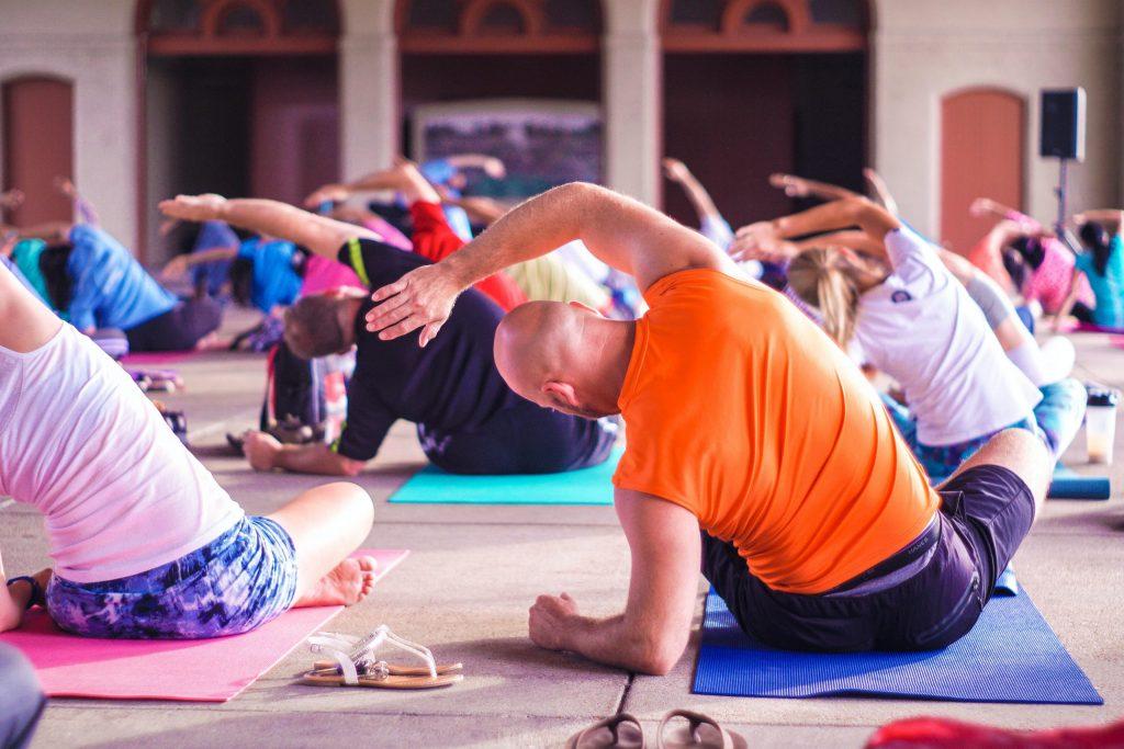 Eine Gruppe Firmen Mitarbeiter beim Yoga auf farbigen Matten