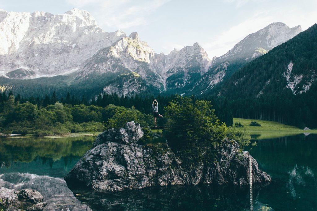 Eine Frau steht für ein Yoga Retreat in den Bergen auf einem Fels mitten im See im Yoga Baum