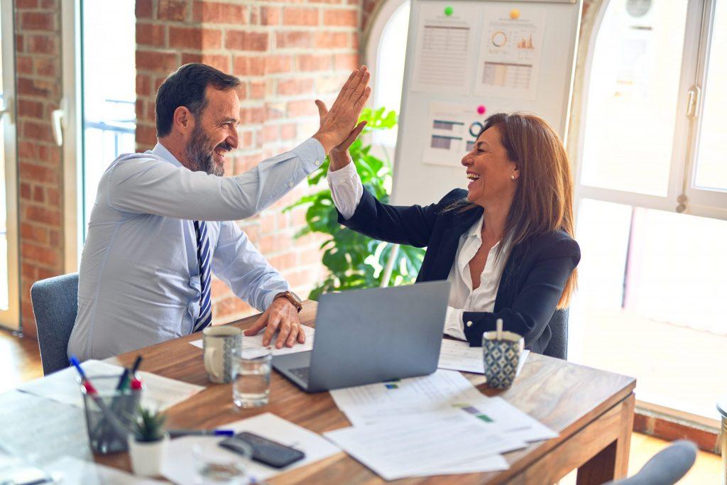 Zwei Führungskräfte (männlich und weiblich) mit guter Laune am Tische sich in die Hände klatschend