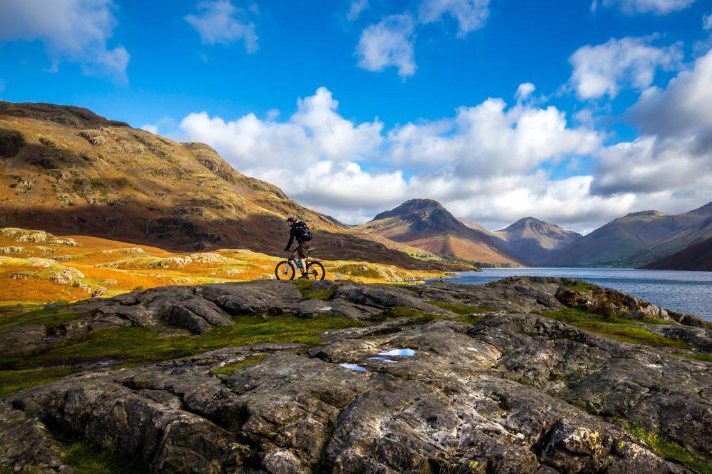 Ein Mountainbiker fährt während Yoga Retreat in den Bergen vor einer Bergkulisse an einem Bergsee vorbei
