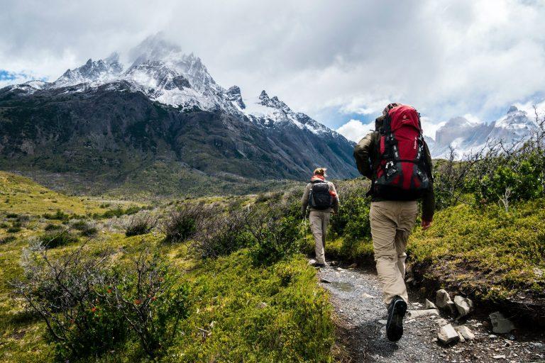 Zwei Wanderer die während Yoga Retreat in den Bergen auf einem Wanderweg in den Bergen laufen