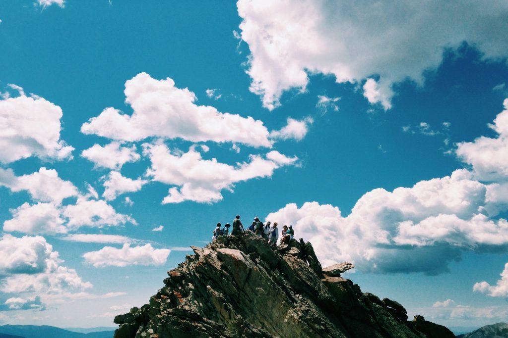 Eine Gruppe an Menschen während des Team Buildings auf einem Berg vor wolkigem Himmel