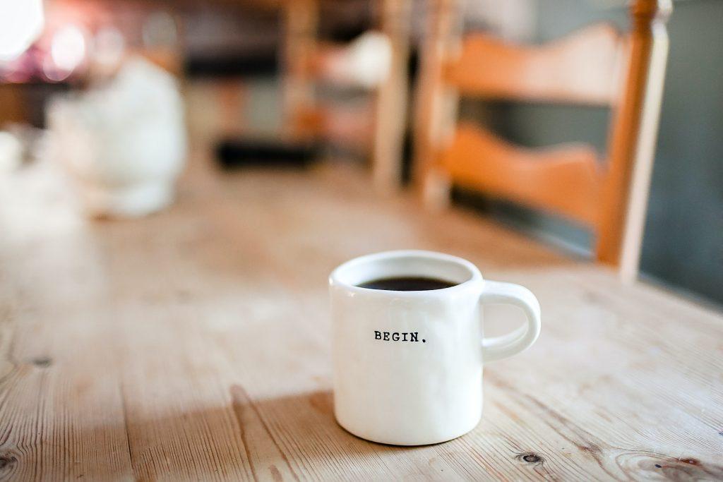 Yoga Einzelcoaching - Weiße Tasse auf Holztisch mit der Aufschrift Begin