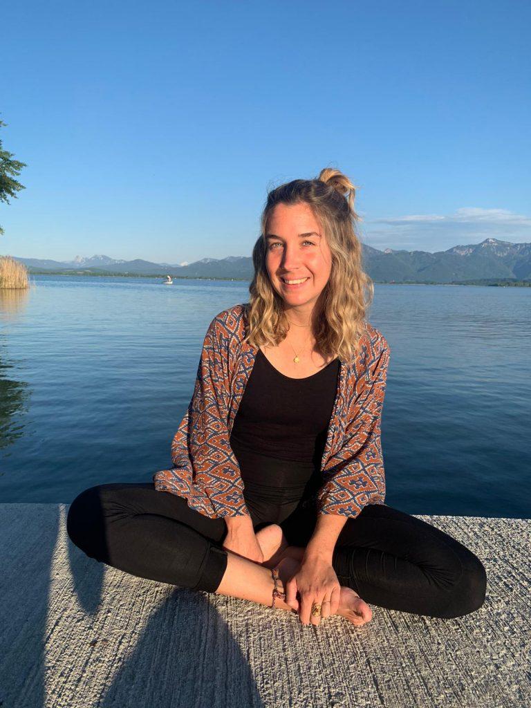 Marie Gerlach - Yogalehrerin im Mountainflow Yoga Studio Bad Reichenhall sitzt vor dem blauen Wasser des Chiemsees auf der Frauninsel